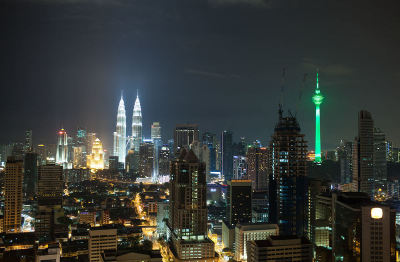 Panorama of Kuala Lumpur at night. Illuminated buildings and skyscrapers in the capital of Malaysia. Menara KL Tower and Petronas Towers dominating over the city architecture Architecture Building Capital City Cityscape Highrise Horizontal Illuminated Kuala Lumpur Menara Metropolis Metropolis Building Modern Night Outdoors Petronas Tower Urban Skyline
