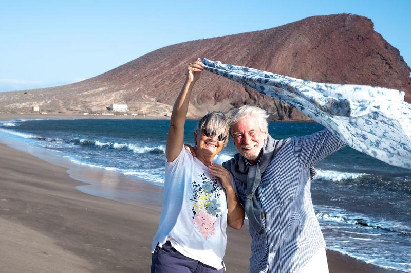 Portrait of senior couple on beach by sea against clear sky