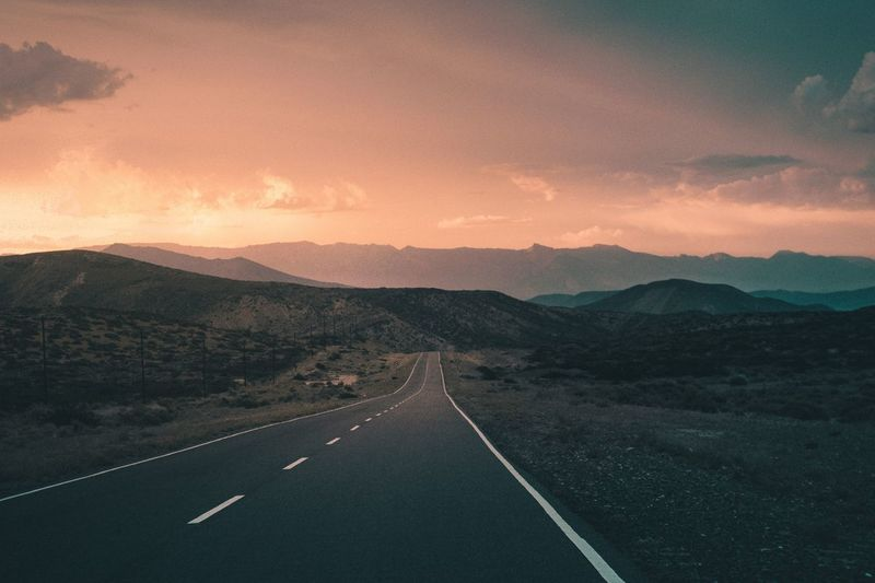 Road leading towards mountains against sky at sunset