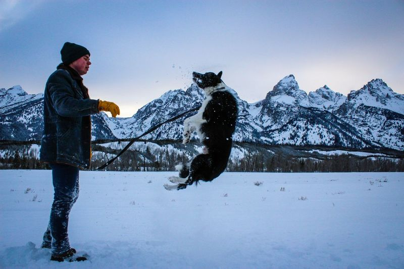 Side view of man playing with dog by mountains on snowy field