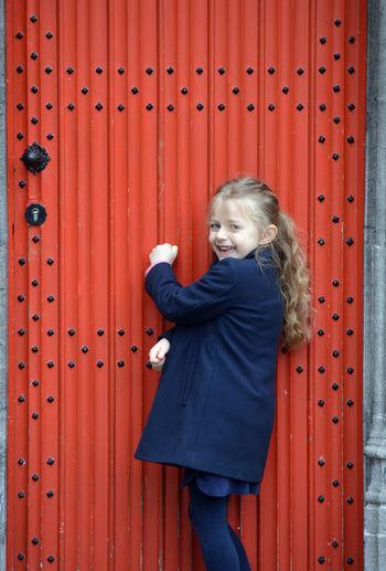 Portrait of cute girl standing against red door