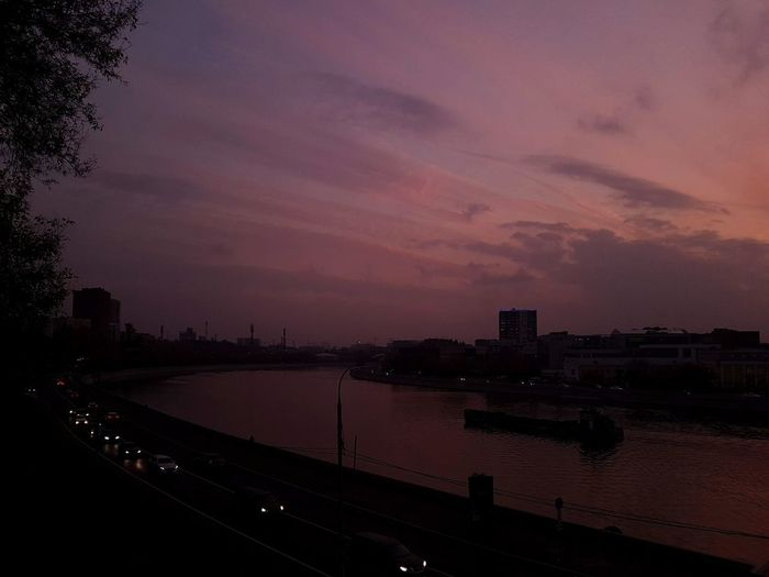 Silhouette buildings by river against sky at sunset