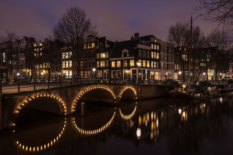 Arch Bridge Over River By Buildings At Night