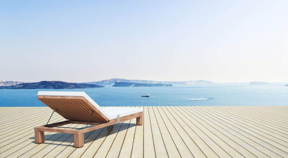 Chaise longue by sea against sky