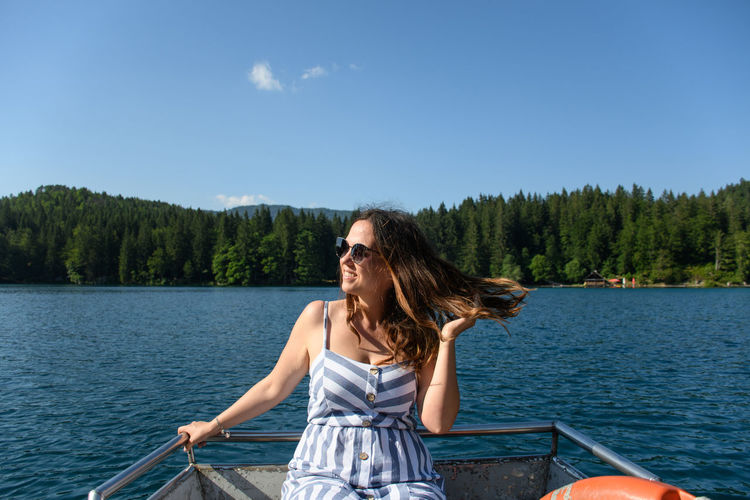 Smiling woman sitting in boat at lake against sky