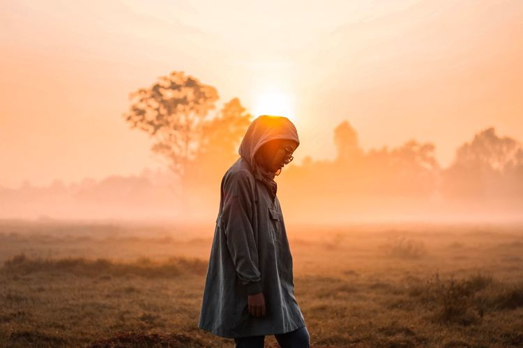 Side view of woman standing on field in foggy weather during sunrise