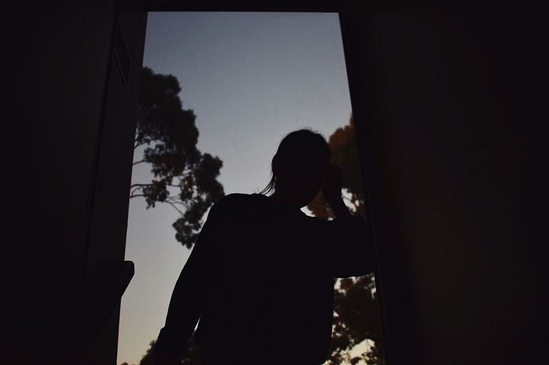 Silhouette woman standing by window in building