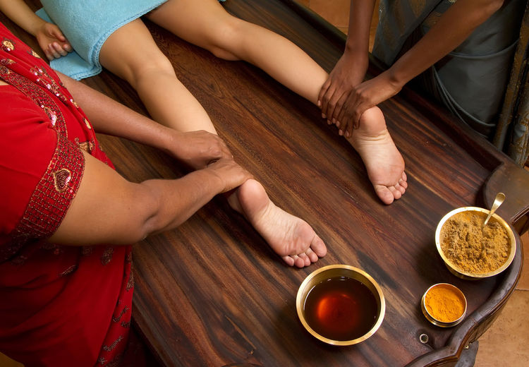 indian doctors doing traditional ayurvedic oil foot massage Adult Ayurveda; Herbal; Finger; Doctor; Tranquil; Skin; Lifestyle; Naked; Sensuality; Recovery; Female; Shoulder; Face; Foot; Satisfaction; Alternative; Pressure; Enjoyment; Clinic; Oil; Comfortable; Wellbeing; People; Spa; Stress; Massaging; Back; Hand; Thumb; Bonding Day Drink Food Food And Drink Freshness Friendship High Angle View Human Body Part Human Hand Indoors  Lifestyles Low Section Men People Real People Sitting Table Togetherness Two People Women Wood - Material Young Adult Young Women
