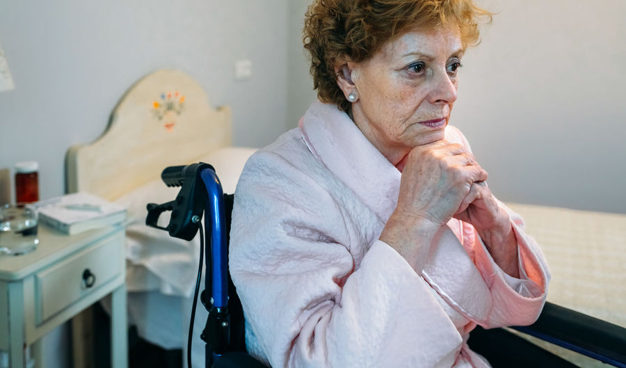 Close-up of senior female patient sitting on wheelchair in hospital
