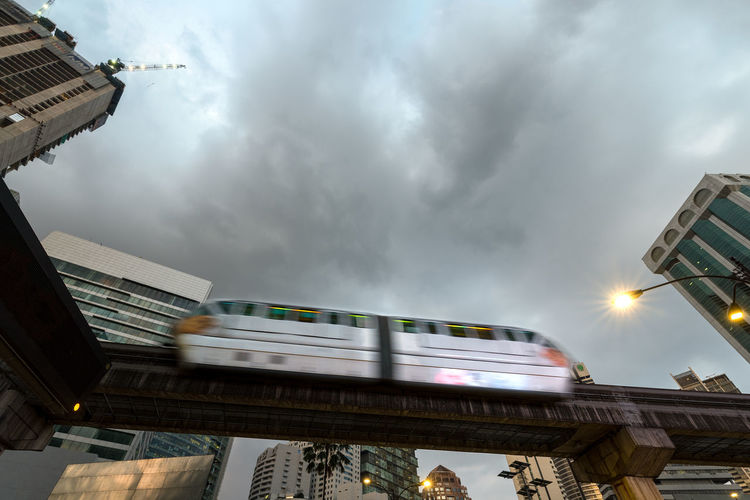 A 2 carriage mono rail sky train passing over over head with city back ground and cloudy skies, Kuala Lumpur, Malaysia. Carriages  Kuala Lumpur Sky Train Architecture Building Exterior Built Structure City Cloud - Sky Day Low Angle View Mode Of Transport Mono Rail Monorail  Motion Outdoors Public Transportation Sky Skytrain Train - Vehicle Transportation