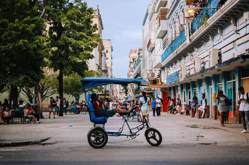 Paseo. City Architecture Transportation Building Exterior Street Real People Built Structure Tree Mode Of Transportation Group Of People Land Vehicle Incidental People Nature Road City Life Women Men Plant Day Sky Outdoors EyeEm Selects EyeEm Best Shots Havana The Street Photographer - 2019 EyeEm Awards