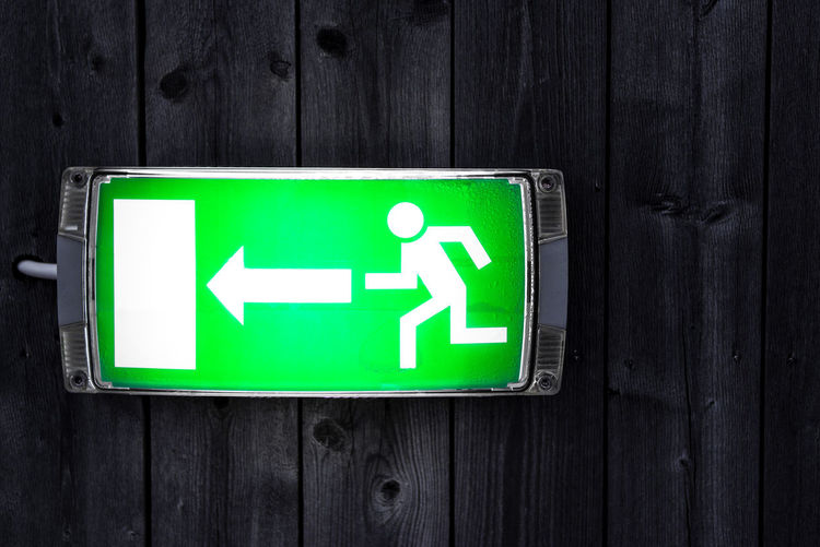 Emergency exit sign on wooden plank wall Arrow Danger Direction Emergency Emergency Exit Escape Exit Glow Green Guide Help Light Rescue Security Sign Symbol Urgency Wall