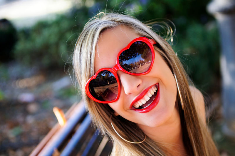High angle portrait of smiling woman wearing heart shape sunglasses at park