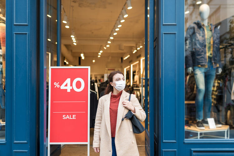 Happy woman wearing mask standing by shopping mall