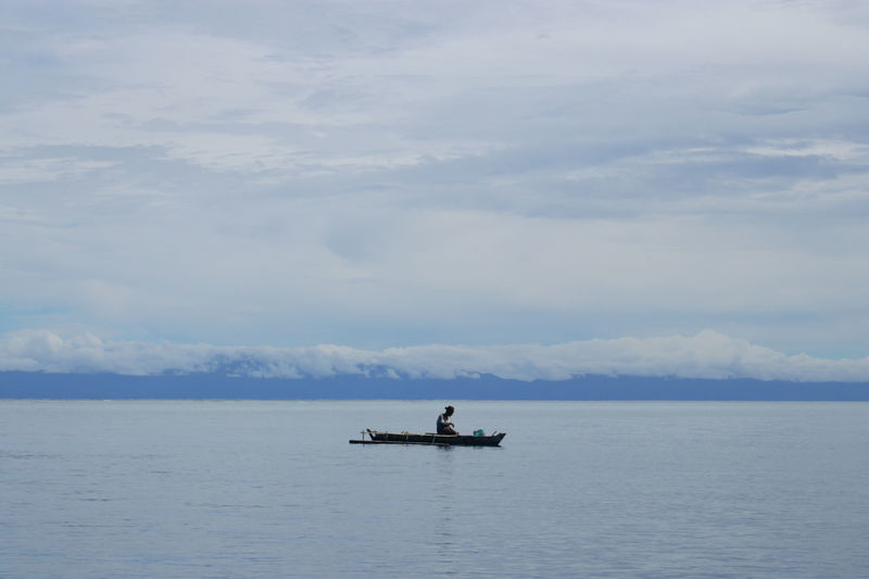 Mid distance view of man on rowboat in sea