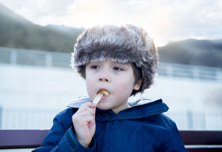 Close-up of boy looking away while eating food outdoors