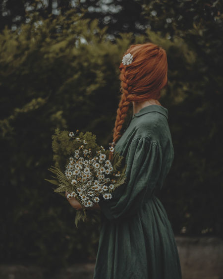 Side view of woman with wild flowers bouquet