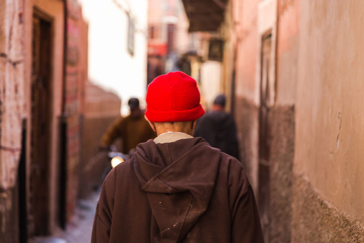 Alley Architecture Building Exterior Built Structure City Clothing Day Focus On Foreground Hairstyle Hat Leisure Activity Lifestyles Men One Person Real People Rear View Red Standing Street Waist Up Walking Warm Clothing