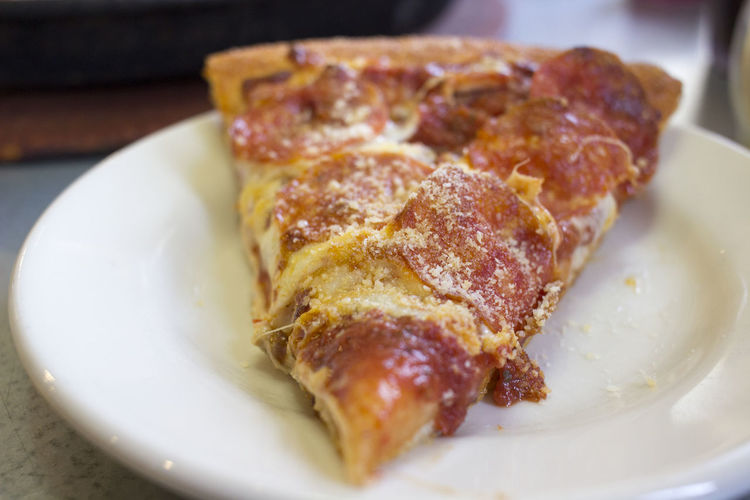 Close-up of pizza slice in plate on table