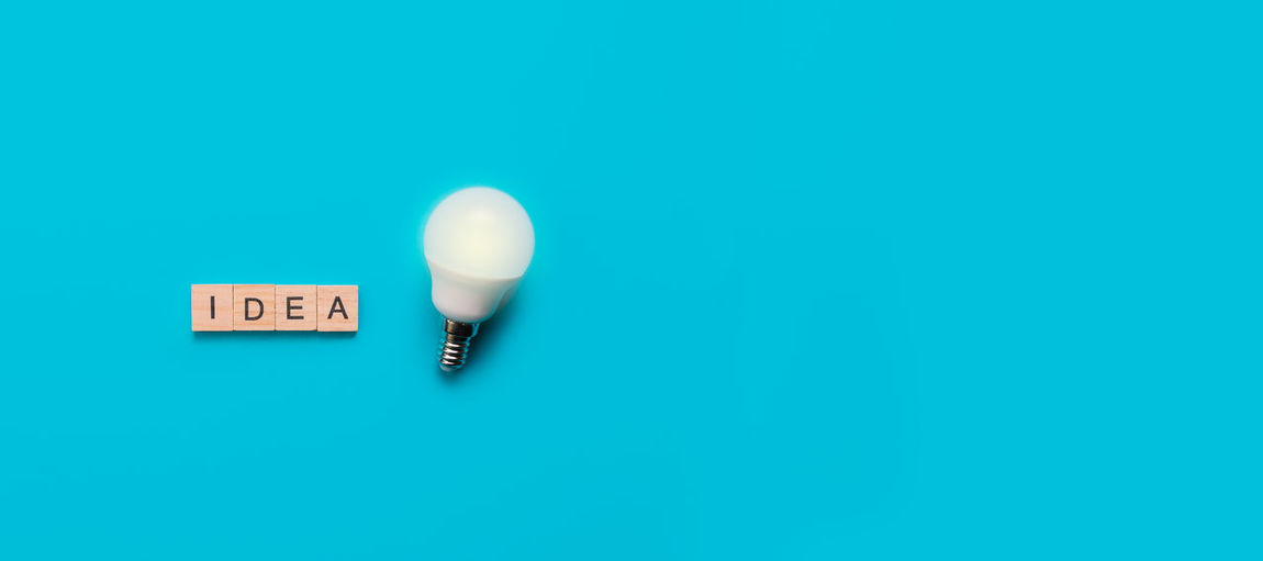 Close-up of light bulb against blue background