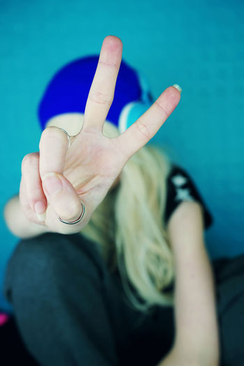 Close-up of woman gesturing peace sign against blue wall