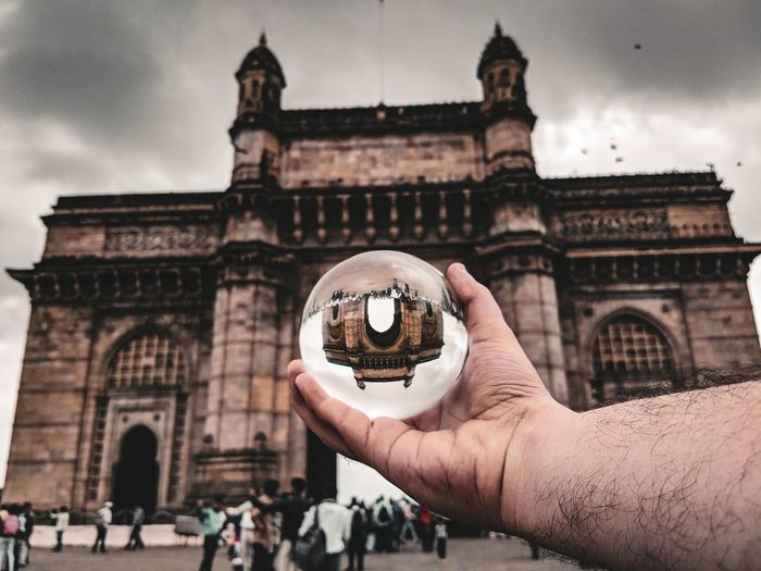 Cropped hand holding crystal ball with gateway of india reflection