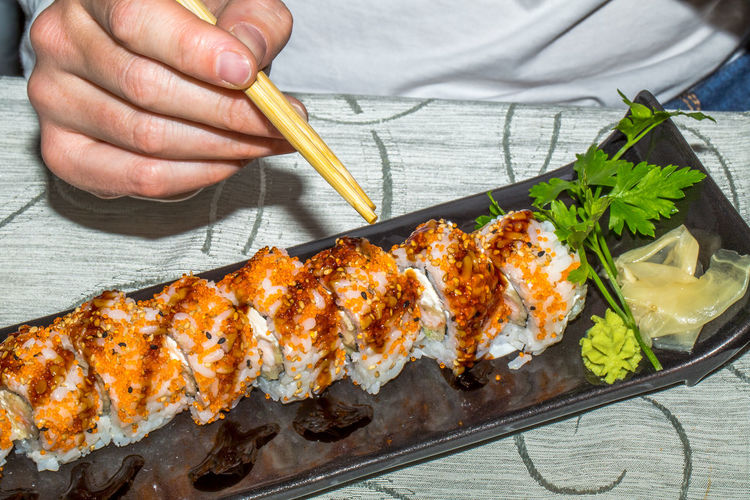 Midsection of man having sushi on table