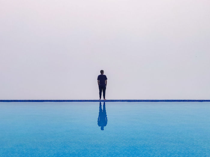 Rear view of standing by infinity pool against sky