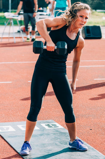 Woman lifting dumbbells on running track