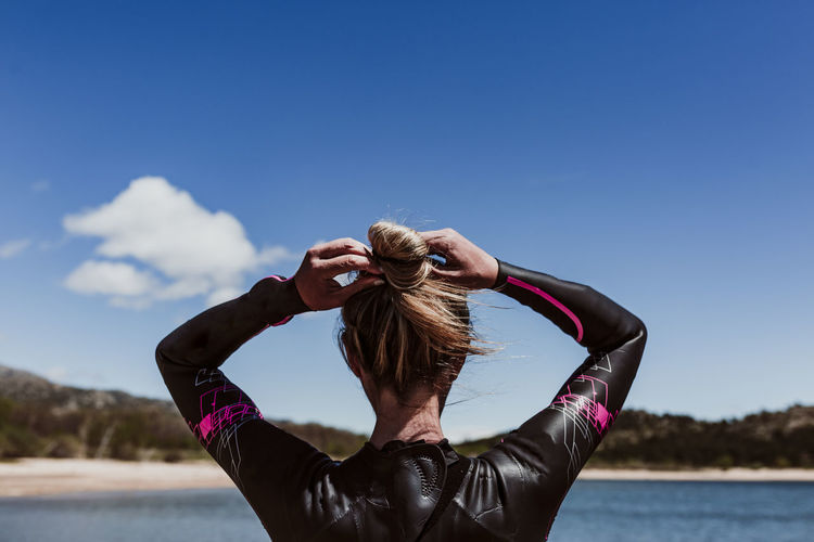Rear view of woman wearing wetsuit at beach
