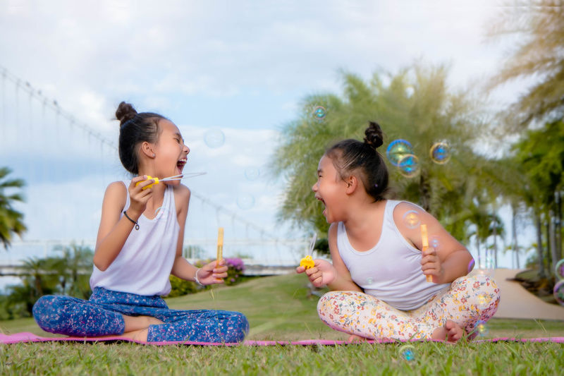 Cheerful girls playing with bubble wand while sitting on field against sky