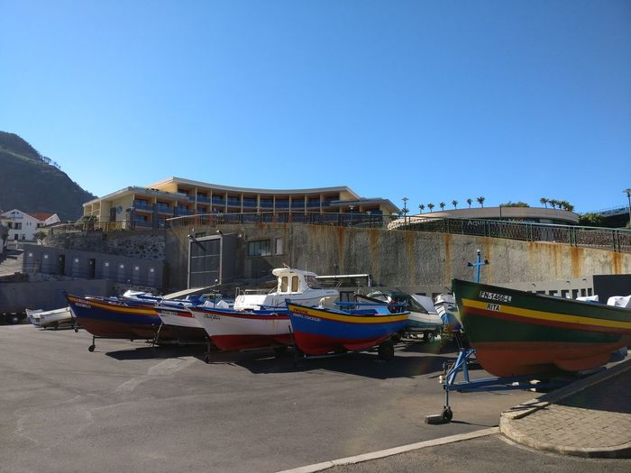 Boats moored on shore against clear blue sky