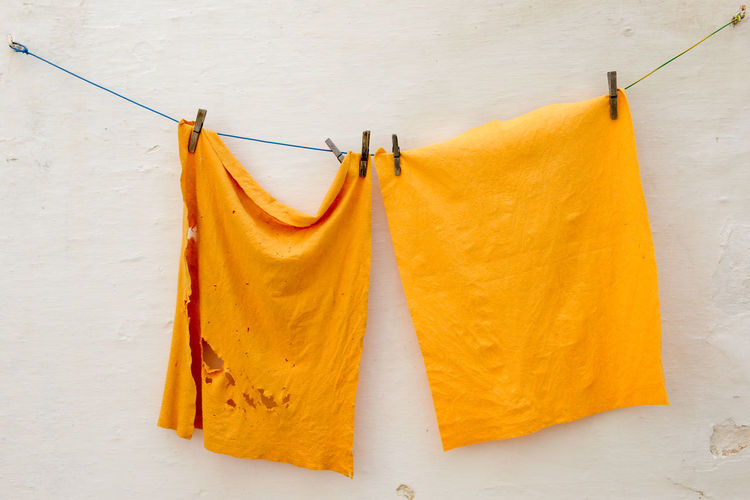 Close-up of clothes drying on clothesline against white wall