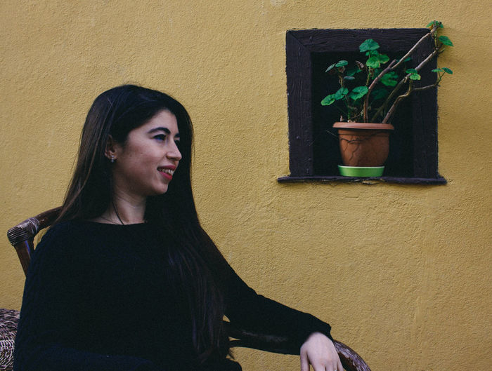 Portrait of young woman against wall with flower