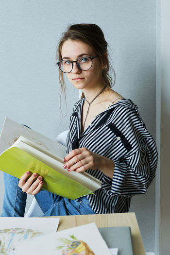 Young woman with eyeglasses on paper against wall