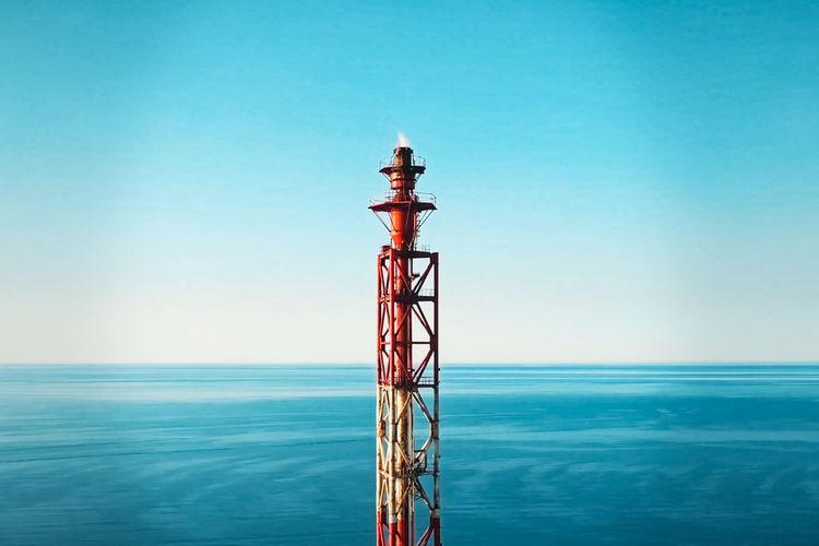 Tower against sea against clear blue sky