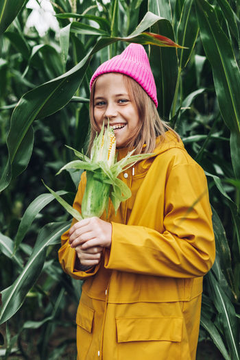 Smiling young woman standing against yellow plants