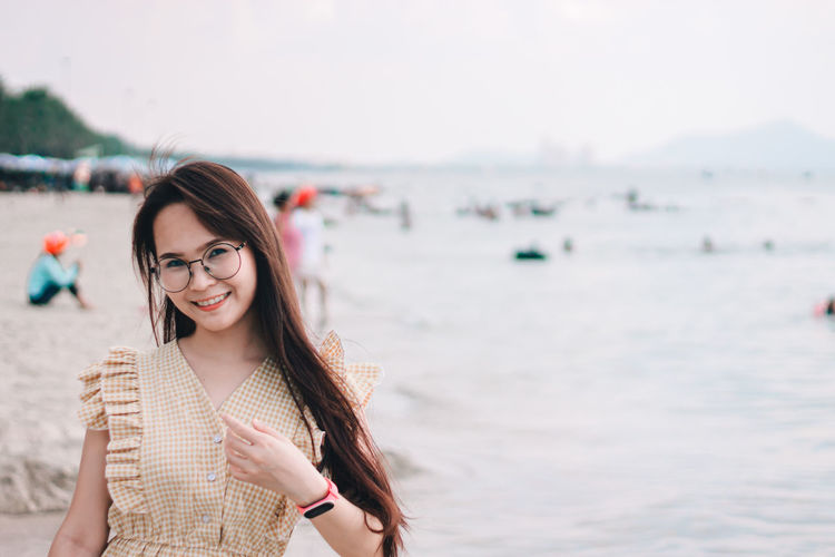 Portrait of beautiful woman wearing sunglasses gesturing while standing at beach