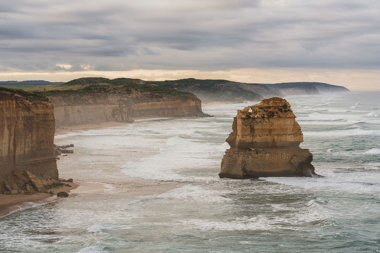 Moody scenery along great ocean road with rock formation on sea shore against sky