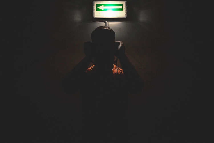 Man in illuminated dark room