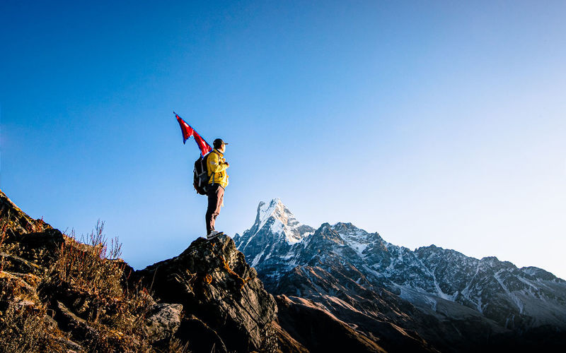 Man holding nepali flag while standing on mountain against clear blue sky
