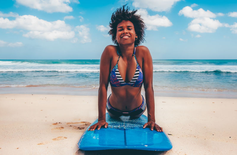 Portrait Of Smiling Young Woman Lying On Surfboard At Beach During Sunny Day