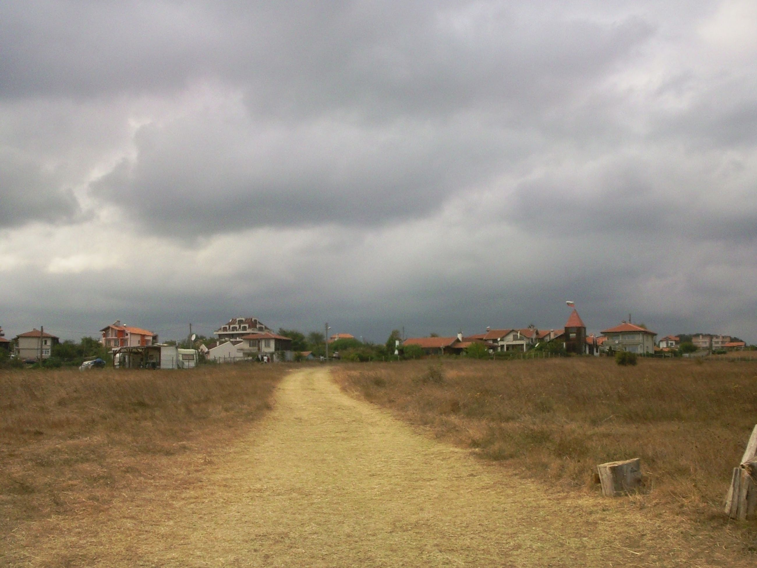 architecture, the way forward, cloudy, built structure, dirt road, cloud - sky, house, tranquility, building exterior, tranquil scene, sky, storm cloud, field, cloud, day, solitude, rural scene, scenics, nature, countryside, outdoors, long, non-urban scene, beauty in nature, no people