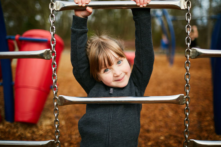 Childhood Child Playground Girls Chain Swing One Person Portrait Smiling Looking At Camera Emotion Women Happiness Females Offspring Holding Outdoor Play Equipment Focus On Foreground Hair Innocence Hairstyle Bangs Jungle Gym