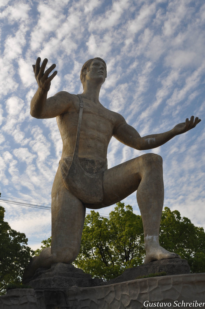 statue, sculpture, human representation, art and craft, male likeness, low angle view, creativity, sky, cloud - sky, day, no people, outdoors, history, architecture, tree