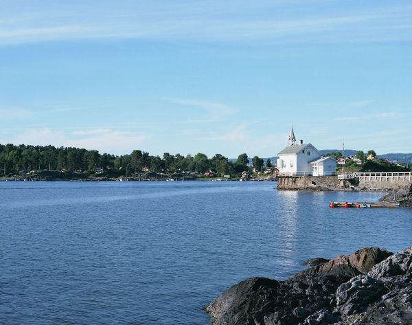 Church by the water on the islands in the inner Oslo fjord Norway Sunny Architecture Beauty In Nature Blue Building Exterior Built Structure Day Film Photography Light Clouds Nature No People Norway Nature Norwegian Landscape Norwegian Nature Outdoors Rocks Scenics Sea Sky Tranquility Tree Water