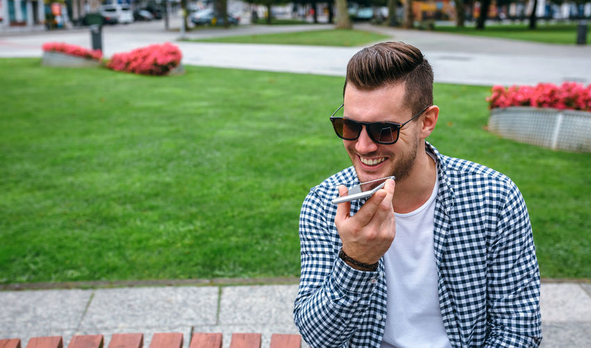 Smiling man using phone while sitting outdoors