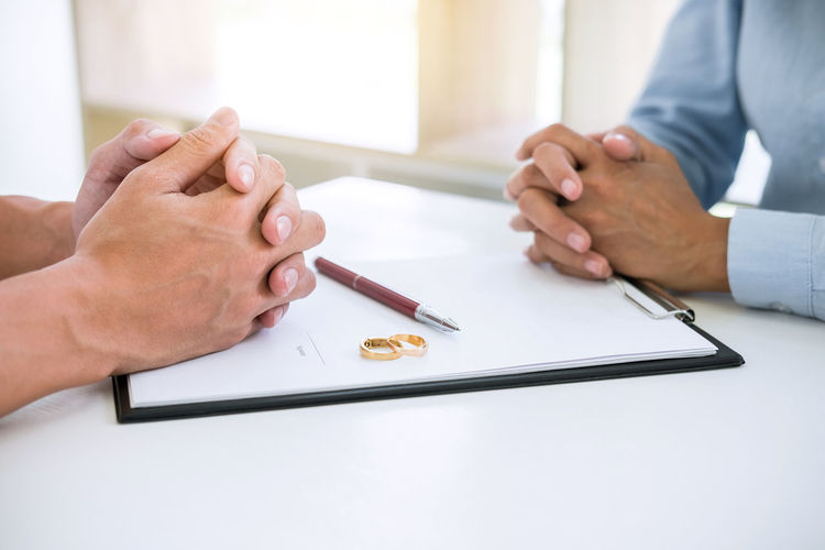 Midsection Of Couple Sitting With Divorce Paper And Rings On Desk In Courtroom