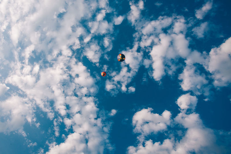 Low Angle View Of Hot Air Balloons Flying Against Cloudy Blue Sky
