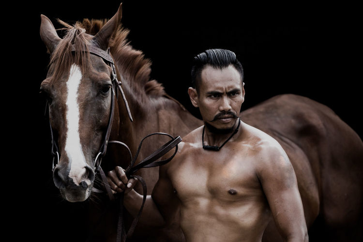 Shirtless muscular man looking away while standing by brown horse against black background